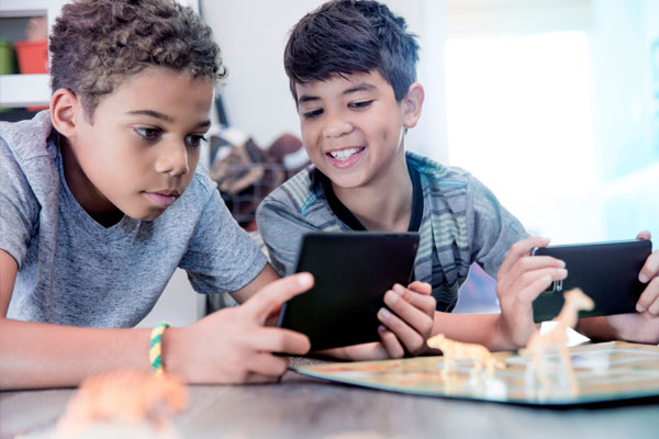 Two boys playing handheld gaming devices